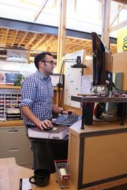 Jamil Malone worked with his father to create his standing desk. Sullivan Higdon & Sink provides employees with adjustable keyboard platforms, and the company gives the standers floormats that Malone says help prevent foot fatigue.