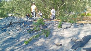 A crew from Wichita's New Image Roofing & Construction repairs storm damage on a roof.