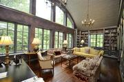 The library has walnut floors, three walls of bookcases, two French chandeliers and antique Italian sconces.