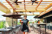 Allie Quade, server at Hi Jax, serves drinks at the rooftop restaurant at Jax Fish House & Oyster Bar in CitySet.