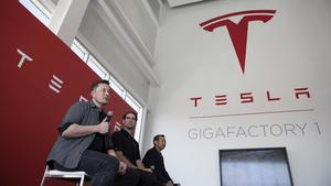 Billionaire Elon Musk, chief executive officer of Tesla Motors Inc., left, speaks as Jeffrey Straubel, chief technical officer and co-founder of Tesla Motors Inc., center, and Yoshihiko Yamada, consultant at Panasonic Corp., look on during a press event a