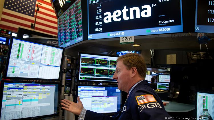 A trader works beneath a monitor displaying Aetna Inc. signage on the floor of the New York Stock Exchange (NYSE) in New York, U.S., on May 20, 2016.