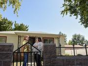 Taryn Lewis, right, housing manager at DURA, talks with homeowner Regina Vigil at her Villa Park neighborhood home in Denver, where rehabilitation projects are under way.