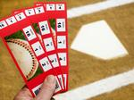 Hand holding Baseball Tickets at home plate