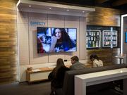 An employee, right, assists shoppers sitting on a couch in front of a DirecTV display inside an AT&T Inc. store in New York, U.S., on Monday, Jan. 25, 2016.