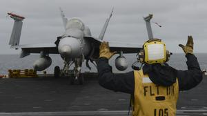 161206-N-DA275-053 PACIFIC OCEAN (Dec. 6, 2016) Petty Officer 3rd Class Christopher Duviella, a native of Brooklyn, N.Y., signals an F/A-18C, from the Death Rattlers of Marine Fighter Attack Squadron (VMFA) 323, on board the aircraft carrier USS Nimitz (C