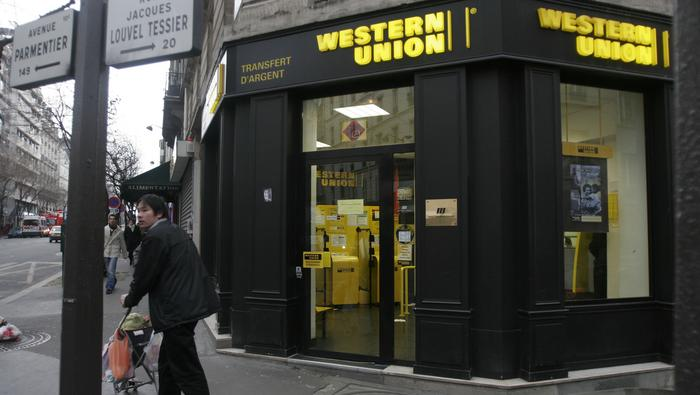 Pedestrians pass a branch of Western Union  near Belleville in Paris, France, Thursday, January 26, 2006. First Data Corp. said it plans to spin off 155-year-old Western Union, the world's largest money- transfer business, as a public company that may be