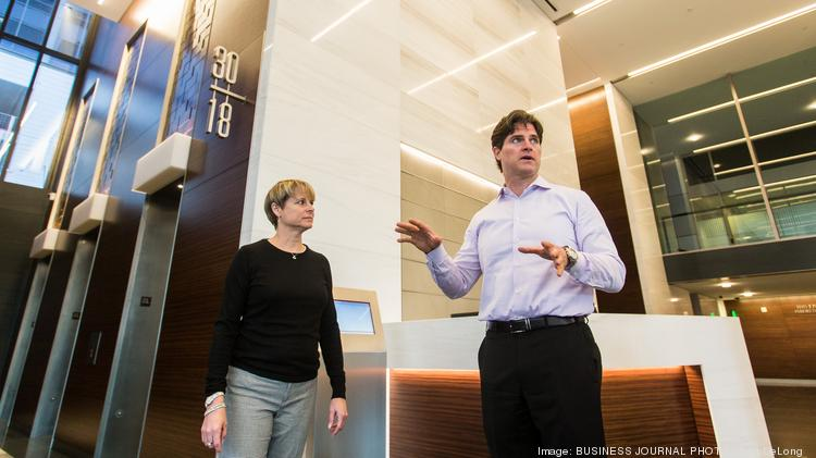 Ty Bennion, senior managing director for Hines in Seattle, talks about some the features of the renovated lobby as Kathy O'Kelley, Hines vice president of property management, in Seattle, listens.