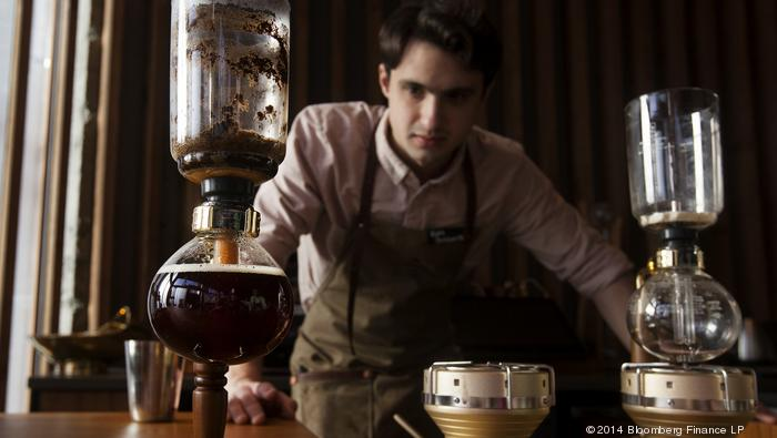 Barista Ryan McDonnell siphons coffee using vintage technology, including heat from a halogen bulb, at the coffee experience bar of the Starbucks Corp. Reserve Roastery and Tasting Room in Seattle, Washington, U.S., on Wednesday, Dec. 3, 2014. The store i