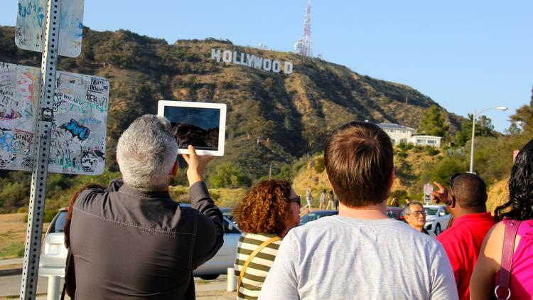 """Tourists take pictures of the Hollywood sign in Los Angeles. (""""tourists and their iPad tablet"""" by David P. Fulmer. Used under Creative Commons BY 2.0 license.)"""