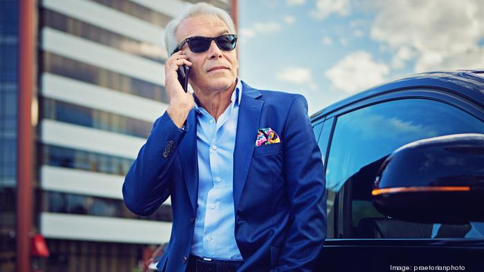 Businessman is talking using his mobile phone standing next to his car