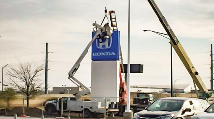 Sign Crews Work Tuesday To Relocate A Monument Sign At Schofield Honda.