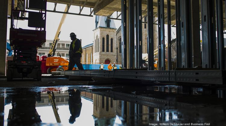 A construction worker is reflected in a puddle on the first floor of the site.