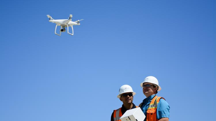 Chris Torres, the technology integration manager for DPR Construction, and Jarvis Worton, a field engineer, operate a drone over the Facebook data center campus in Fort Worth. The drone aids in the development of the campus.