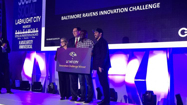 Fixt CEO and co-founder Luke Cooper, middle right, celebrates after winning the Baltimore Ravens sponsorship package with, from left, Light City Baltimore volunteer Jamie McDonald, Ravens executive Kevin Rochlitz and Ravens safety Eric Weddle.