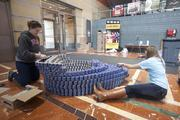 Lauren Buffenbarger, left, and Kristin Plummer carefully lay out cans as they build a high-heeled shoe in the window at the Aronoff Center for the Arts. They are working with the team from MSA Architects.