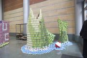A fish jumping from water was built using cans that have green and yellow labels. The water surrounding the fish is made of blue bags of beans.