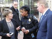 Seattle Police Capt. Deanna Nollette (left) speaks to Deputy Chief of Police Carmen Best (center) while Mayor Ed Murray (right) stands nearby after a press conference about the ongoing investigation into the shooting of police officers.