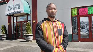Activist Wyking Garrett stands in front of Earl's Cuts and Styles barbershop in the Midtown Center in the Central District of Seattle, Wash. on Apr. 20, 2017.