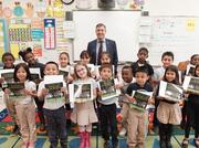 """Brown poses with first-grade class after reading them Ally's new book called """"Planet Zeee and the Money Tree."""""""