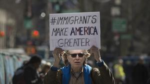 A demonstrator holds a sign while marching to accompany immigration activist Ravi Ragbir, not pictured, to a check-in with Immigration and Customs Enforcement (ICE) at the Jacob K. Javits Federal Building in New York, U.S., on Thursday, March 9, 2017. Rag