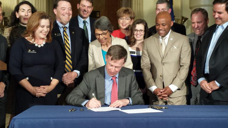 Colorado Gov. John Hickenlooper signs a construction-defects reform bill Tuesday while surrounded by legislative sponsors and supporters of the effort.