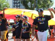 U.S. Bank Colorado market president Hassan Salem (far right) holds up a corner of a large rainbow flag while marching in PrideFest Sunday.