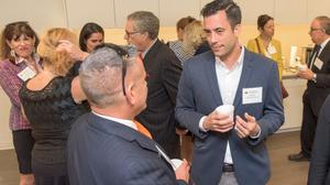Ian Torres of That Marketing Agency, center, speaks with Jorge Acosta of USI Insurance, left.