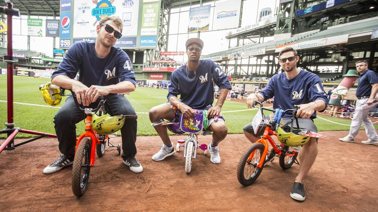 (Left) Milwaukee Brewers Jett Bandy, Keon Broxton and Eric Sogard show off the bikes they helped build recently for kids from the Next Door Foundation.