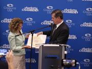 Gov. Roy Cooper presents Harriet Harty, executive vice president of human resources at Allstate, with a bowl that has the North Carolina seal.