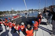 Sixth-grade students from Rio Del Mar Elementary school listen to an O'Neill Sea Odyssey instructor while seated around an open area on a catamaran, which allowed those on the boat to look directly into the Monterey Bay.