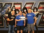 Vet Tix partnered with the band Kiss last year for a 30-city concert tour. The band hired a VetTixer at each event as a roadie. This photo taken at the kick-off event where they met the band. (l-r) Steve Weintraub, chief strategy officer; Jason Conviser, director of Hero's Wish, and Alan Dropkin, director of ticket operations; with the members of Kiss in the background.