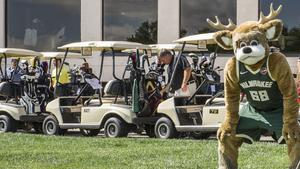 Former Milwaukee Bucks player Vin Baker practices his putting under the watchful eye of Bango during the team's annual golf fundraiser this week at Westmoor Country Club in Brookfield.
