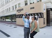 Birmingham residents pose for a picture with a large replica of an Amazon shipping box.