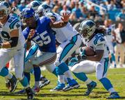 New York Giants linebacker Keith Rivers loses his helmet in pursuit of Carolina Panthers running back DeAngelo Williams.