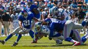 Carolina Panthers running back DeAngelo Williams dives forward, surrounded by tacklers.