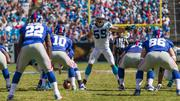 Carolina Panthers linebacker Luke Kuechly yells instructions out to his teammates as New York Giants quarterback Eli Manning gets ready to start a play.