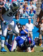 Carolina Panthers defensive end Charles Johnson celebrates a sack against New York Giants quarterback Eli Manning.