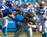 Carolina Panthers wide receiver Steve Smith tries to evade New York Giants linebacker Mark Herzlich after making a catch.
