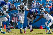 New York Giants running back David Wilson braces for impact as Carolina Panthers defenders close in.