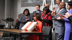 Mayor Catherine Pugh holds up a box that she placed her formal letter to Amazon in.