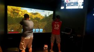 Players try out a shooting simulation at Modern Round in Lucky Strike.