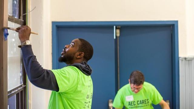 Andre Wright paints puts a new coat of paint on a window frame in the Sharswood Athletic Rec Center.