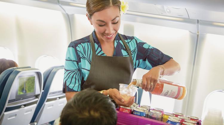 Hawaiian Airlines Flight Attendant Serves The Signature Cocktail