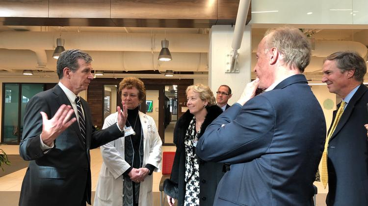 Gov. Roy Cooper speaks with Dr. Mary Claire O'Brien, professor of emergency medicine and senior associate dean for health care education; Dr. Julie Ann Freischlag, the chief executive officer of Wake Forest Baptist Medical Center; and Eric Tomlinson, president of the Innovation Quarter.