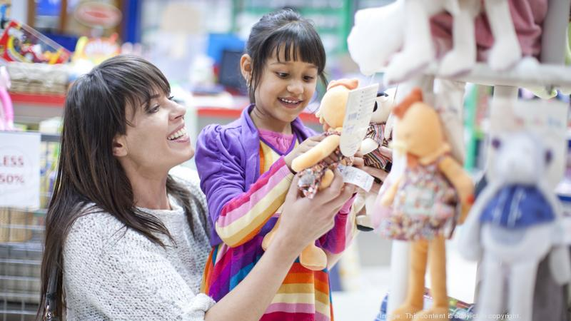 Mother and daughter looking at soft toys in toy shop