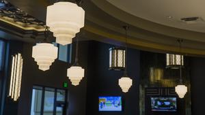 The lounge and lobby of B&B Theatres Longview 7 in Lee's Summit features art deco lighting fixtures.