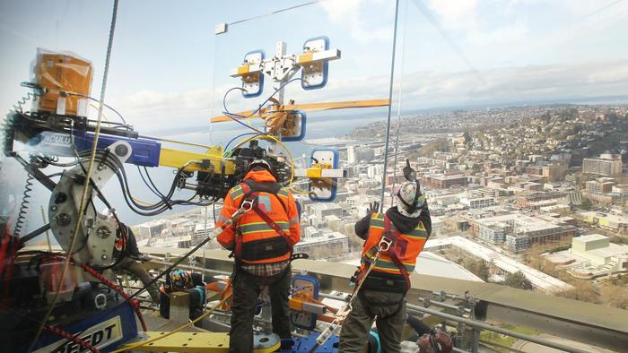 A Herzog Glass team carefully manipulates a custom-built Breedt robotic device to emplace one of the massive one-ton glass panels along the perimeter of the Space Needle during Century Project construction. Each one of the panels have to be hoisted from g