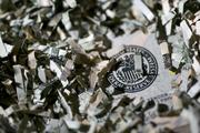 Shredded currency surrounds the seal of the U.S. Federal Reserve.