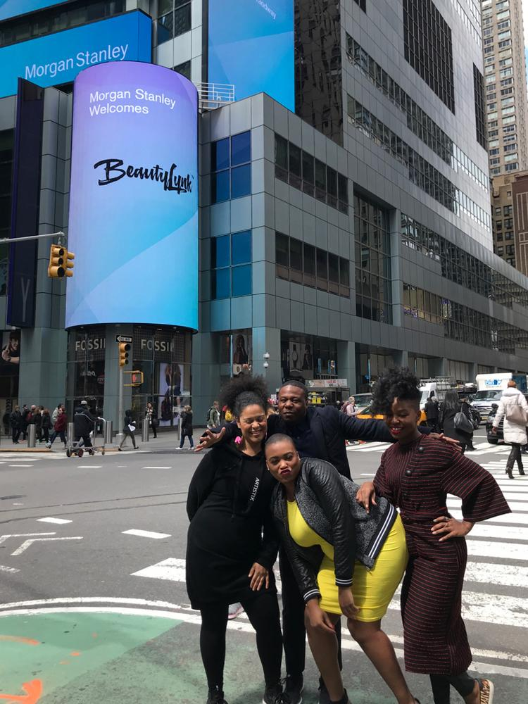 BeautyLynk co-founder Rica Elysee (center) poses in front of the startup's billboard ad in Times Square.